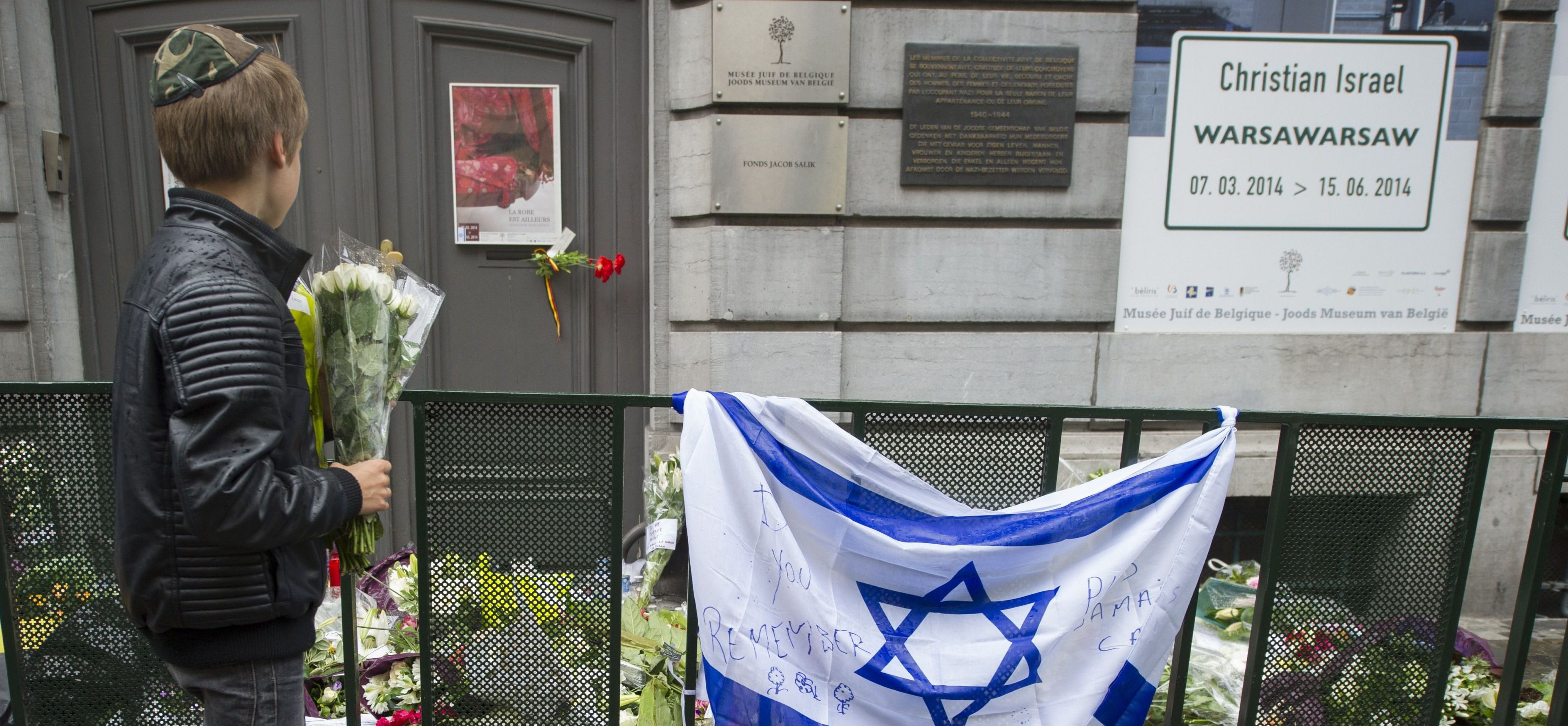 A Jewish boy stands with flowers in front of an Israeli flag and flowers laid in front of the Jewish Museum in Brussels on May 26, 2014, two days after a fatal shooting attack.