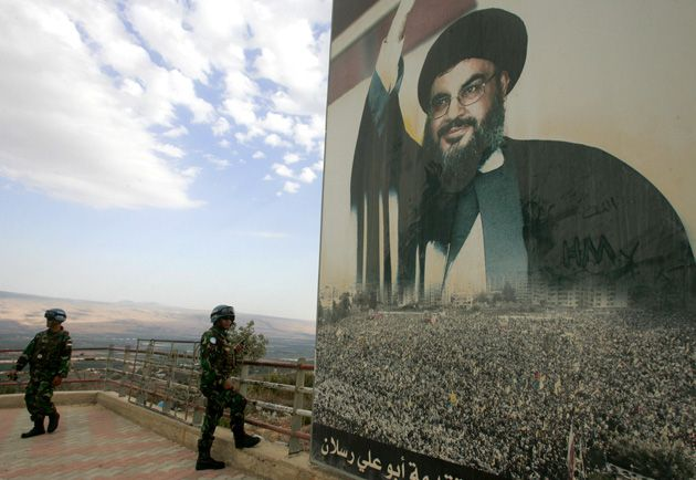 A Looming Presence: U.N. peacekeepers, stationed near Lebanon?s border with Israel, stand next to a poster of Hezbollah leader Hassan Nasrallah.