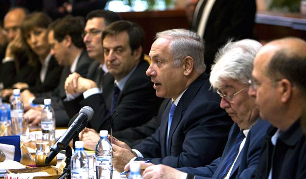 Amplified Ambitions: Israeli Prime Minister Benjamin Netanyahu, at microphone, explains his plans while surrounded by his cabinet, the largest in Israeli history.