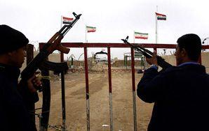 Iraqi guards patrol the Iran-Iraq border east of Basra, as a pair of Iranian flags flutter between those of Iraq