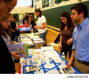 ALL OPTIONS ON THE TABLE: Parents and students talk with representatives from universities and Israel programs at a recent college fair hosted by the Solomon Schechter School of Westchester.