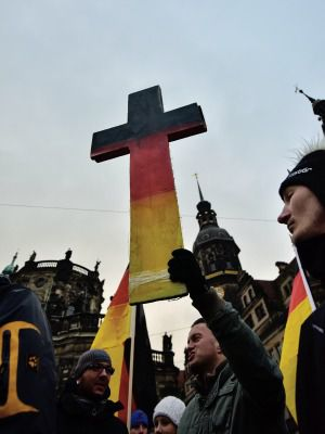 Pegida supporters hold a cross at a January rally in Dresden.