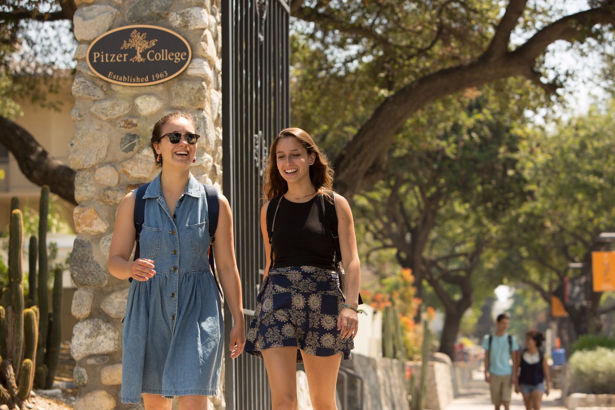 Students walk through the Pitzer College gates.