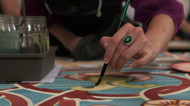 Evelyn Tauben paints a flower on a ceiling panel of a replica of a Polish synagogue.