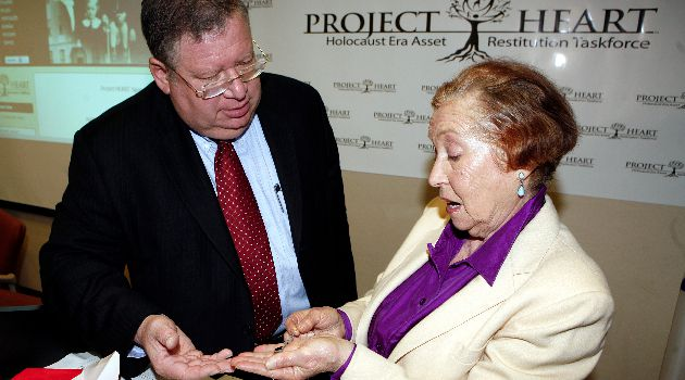Project HEART executive director, Bobby Brown, left, shows Holocaust survivor, Esther Widman, a necklace believed to be recovered from Lodz, Poland.
