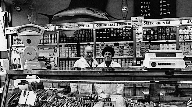 New York Staple: Russ & Daughters has been a constant on the Lower East Side for more than 100 years. Here, Anne (Russ) Federman and Herb Federman stand proudly behind their smoked fish counter around 1970.