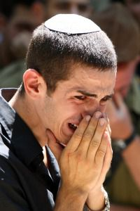Israeli Sorrow: Man struggles with emotion at funeral for victims of terror attack near Eilat.