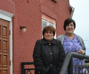 Sold: Judy Witek, left, and Lenore Levine stand in front of the synagogue in Massena that was sold for $1 to the town?s chamber of commerce.