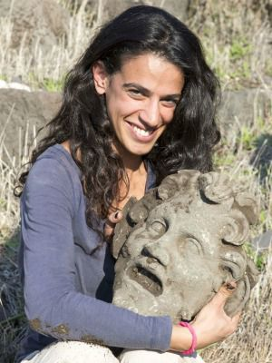 A member of the archaeological team holds the bronze mask of the god Pan, uncovered at the University of Haifa's excavation at Hippos-Sussita.