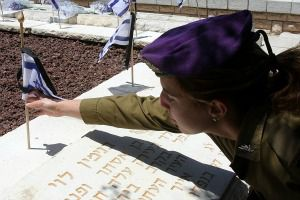 Global Call: Israeli soldier places a flower on a grave for memorial day.