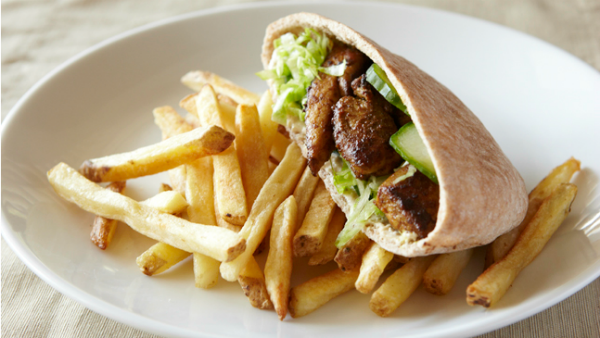 Chicken schwarma in a pita served over a bed of fries.