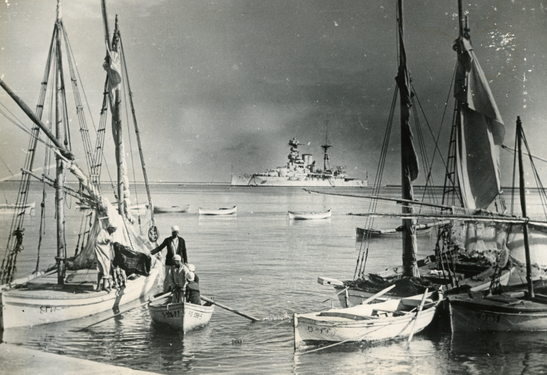 British Protectorate: A photograph of the Suez Canal in Egypt during World War II with the British warship Barham standing guard and a number of fishing crafts getting ready to put to sea.
