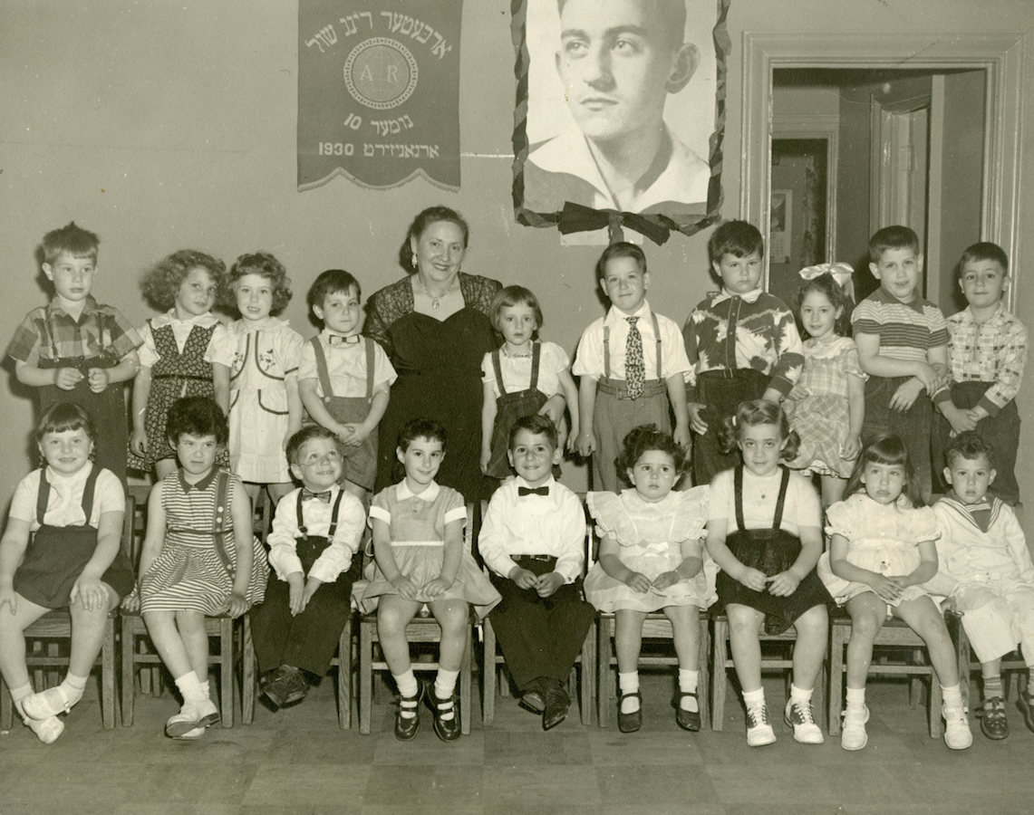 Kindergarten: Class photo of Workmen's Circle School Number 10 in the Bronx showing children posing beneath the image of Warsaw Ghetto uprising and Jewish Labor Bund hero Mikhl Klepfisz.
