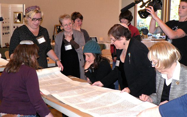 Finished Product: Around the table, clockwise from bottom left: Rabbi Rachel Schoenfeldt, one of the checkers of the Torah; Scribe Rabbi Hanna Klebansky; Kadima liturgist Sandra Silberstein; Scribe Julie Seltzer; Scribe Linda Coppleson and Scribe Irma Penn studying the Torah before attaching it to the eitzim, or wooden spindles, that hold it.
