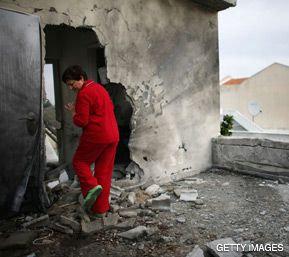NO SHELTER: Maya Iber inspects damage to her Sderot home from a rocket fired December 21 from Gaza.