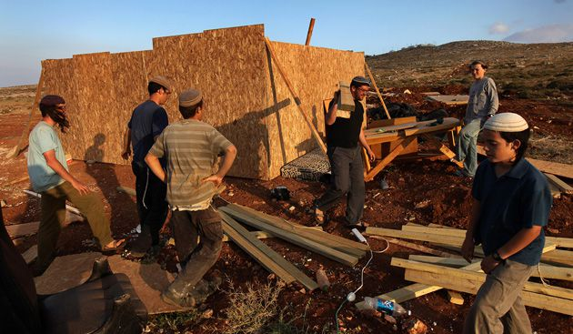 A time to tear Down, A time to Build Up: Shortly after it was demolished by the Israeli mili-tary, settlers rebuild an illegal outpost in the West Bank on May 24.