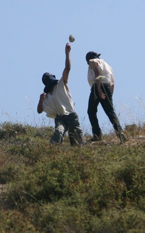 Masked Israeli settlers from the Yitzhar settlement throws stones at Palestinian villagers.