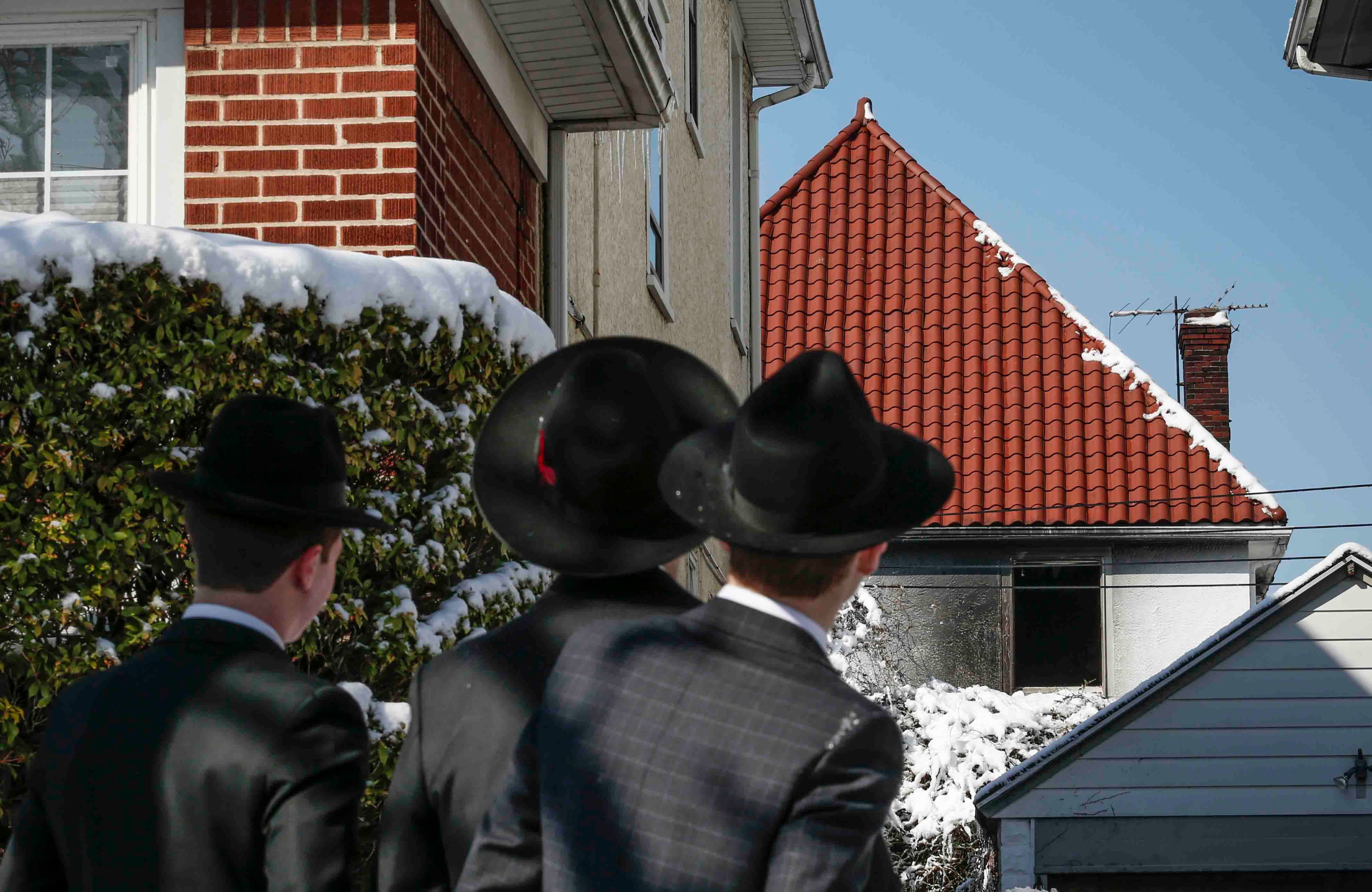 Orthodox Jews gaze at Brooklyn home destroyed by fire started by a malfunctioning hot plate left on over Shabbat.