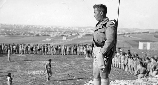 Growing the State: An armed man stands guard at a meeting of young pioneers in Palestine (1938).