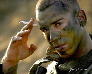 Under Fire: An Israeli soldier smokes a cigarette as he waits for orders to enter southern Lebanon during the war against Hezbollah in 2006