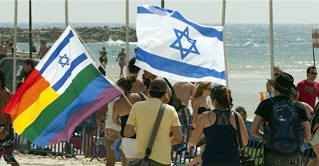 Gay Oasis:  Israelis carry flags during last year?s gay pride parade in Tel Aviv.
