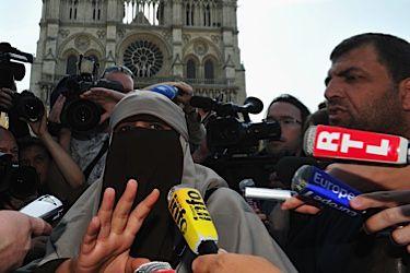 French Fashion? Kenza Drider speaks to the media in front of Paris?s Notre Dame Cathedral on April 11, defying a new French law banning the wearing of full-facial veils in public. She became the first person arrested under the new law.