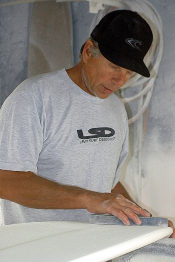 Hang Six (Points): David Levy smoothes a surfboard that he custom-makes in his shop in Narragansett, R.I. He inscribes a Star of David on the underside of the board.