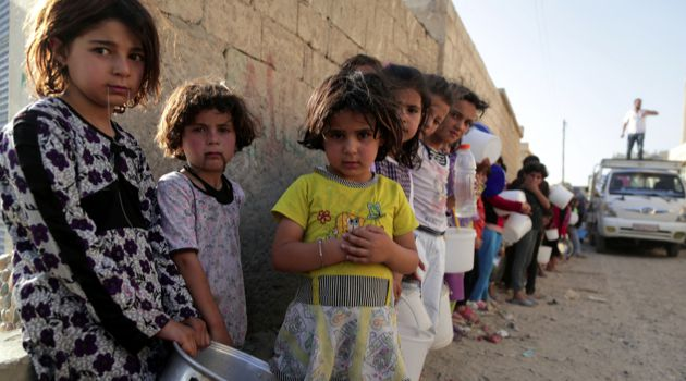 The Ignored?: Syrian children wait in line to collect a free Iftar meal in the northern city of Raqqa during the Muslim holy month of Ramadan on July 14.