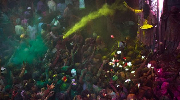 Beyond Belief: A Hindu priest throws color onto Hindu devotees during Holi celebrations at the Bankey Bihari Temple on February 28, 2010 in Vrindavan, India.