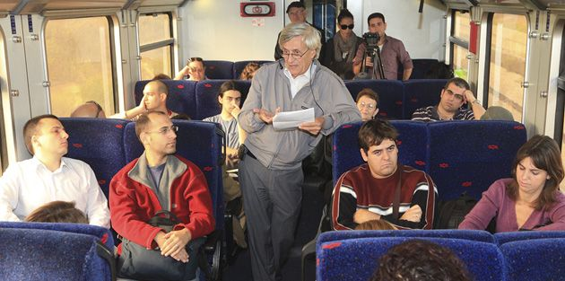 Listen and Learn: Commuters on a train in Jerusalem take in a lecture on the way to their destinations.