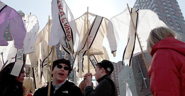Remembrance: Marchers in Lower Manhattan carry shirtwaists emblazoned with the names of those who died in the Triangle fire to mark its 100th anniversary.