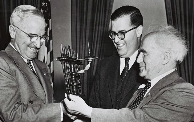 A Great Miracle Happened Here: David Ben-Gurion, right, presents a Hanukkiah to President Harry Truman in 1951. Israeli ambassador to the United States Abba Eban enjoys the moment.