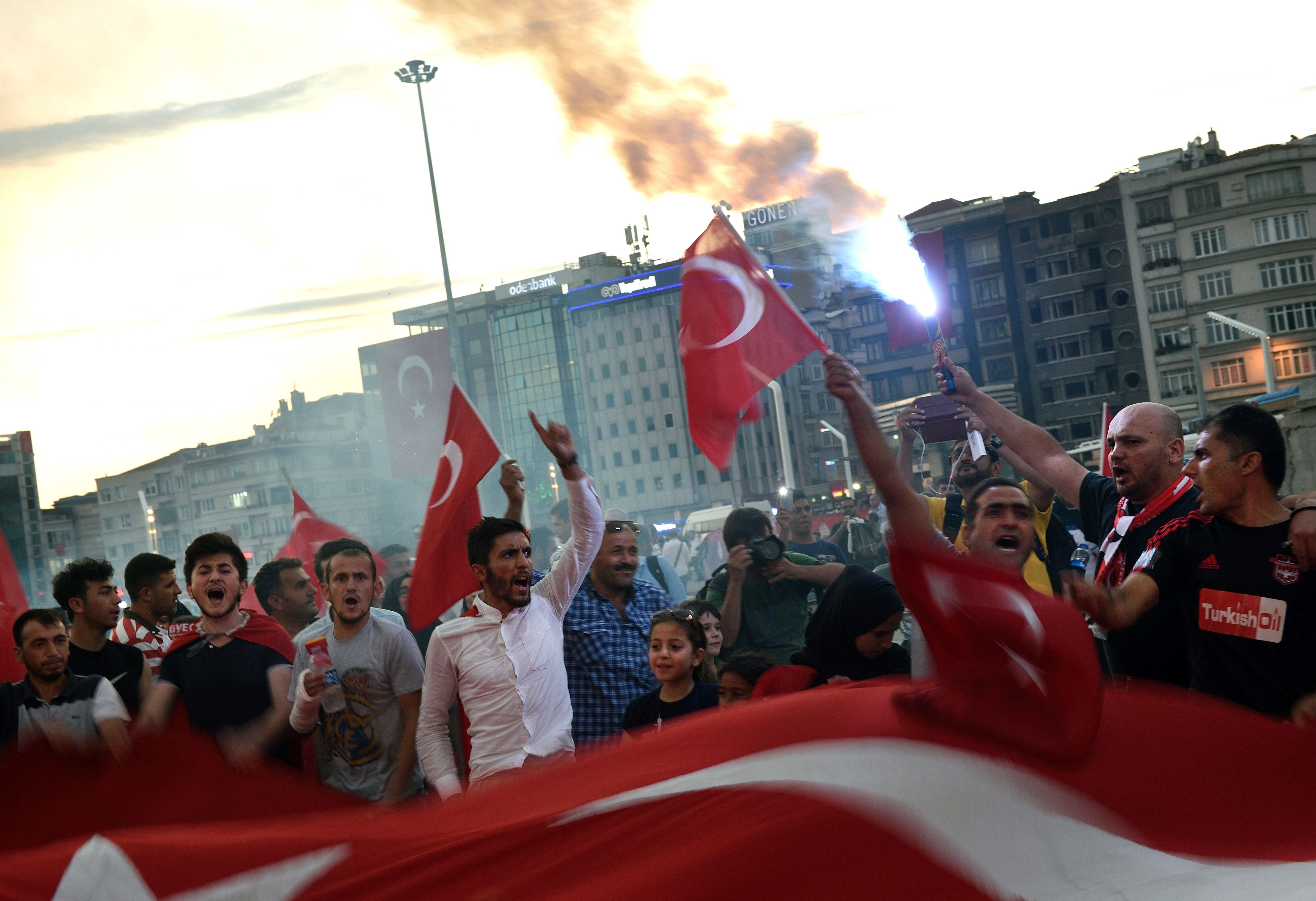 People shout, gestures and hold Turkish national flags as they gather in Taksim square in Istanbul, on July 18, 2016 following the military failed coup attempt of July 15.