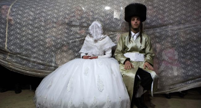 Old World: Jewish bride Rivka Hannah (Hofman) sits next to her groom Aharon Krois during the Mitzvah Tans dance ritual following their wedding in an ultra-orthodox neighborhood of Jerusalem on February 18.