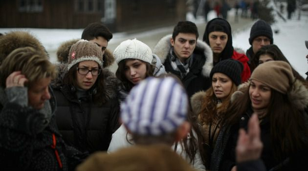 A guide tells visitors about the horrors of Auschwitz.