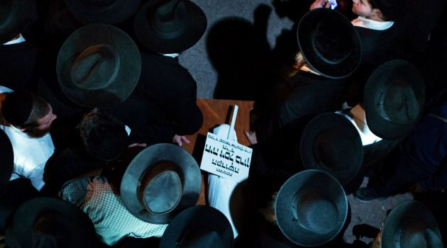 'Pure Soul' Ultra-Orthodox mourners gather at funeral for Chaya Zissel Braun, the infant who was killed in an attack on Jerusalem's light rail train system.