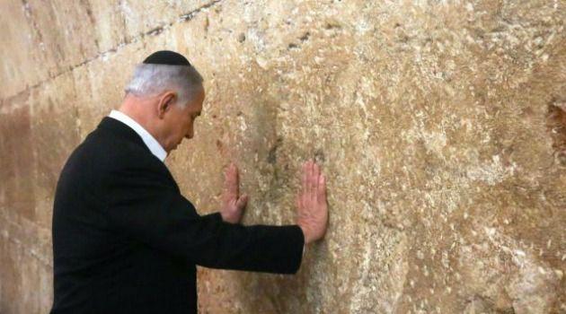 Israeli Prime Minister Benjamin Netanyahu prays at the Western Wall ahead of his trip to the U.S.