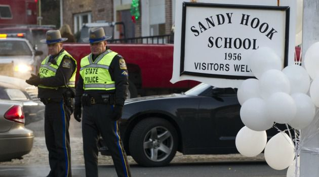 Crime Scene: Police stand guard outside the elementary school in Newtown, Conn., where a young man carried out one of the worst mass killings in U.S. history.