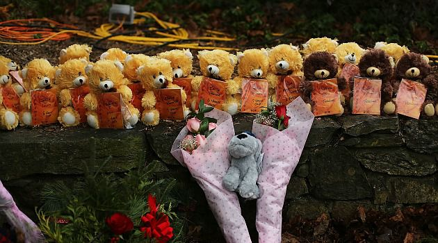 Stricken by Grief: Teddy bears and flowers grace a makeshift memorial to the victims of the rampage in Newtown, Conn.
