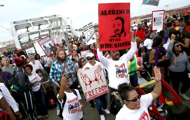 Alabama Still Dreaming: Marchers carry signs as they walk across the Edmund Pettus Bridge during the 50th anniversary commemoration of the Selma to Montgomery civil rights march.