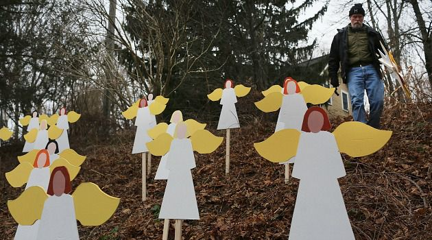 Fallen Angels: Eric Mueller places 27 wooden angels he made in his yard down the street from the Sandy Hook School in Newtown, Conn.
