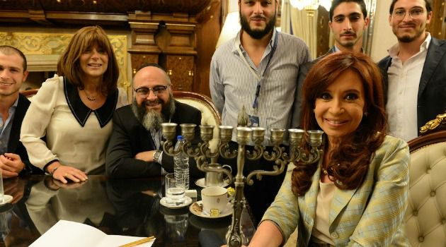 Oddest Godson: Argentine President Christina Fernandez lighting Hannukah candles with the family of Shlomo and Nechama Tawil, whose son became the first Jewish boy adopted under a law intended to counteract an old Argentine legend.