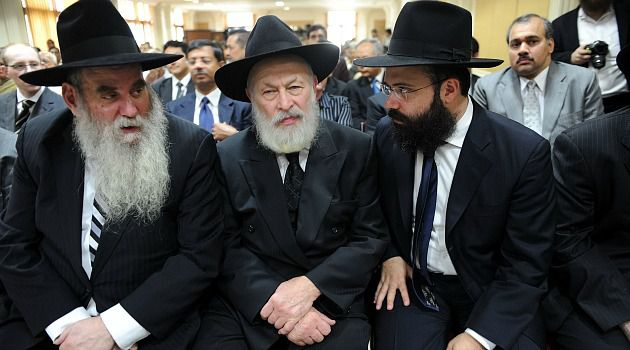 Transition Time? Rabbi Moshe Kotlarsky (left) and Rabbi Yehuda Krinsky (center) join Rabbi Abraham Berkowich in Mumbai, India, at a November 2009 memorial service for a Chabad family slain in a terrorist attack.