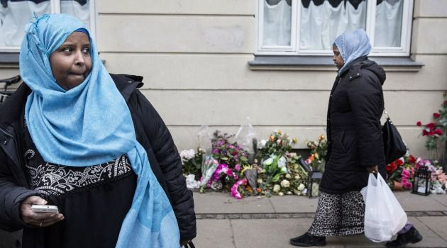 Muslim women walk by flowers left at site where suspected terrorist gunman was killed by Copenhagen police.