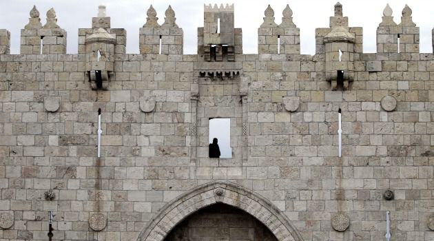 Scene of the Crime: An Israeli security officer monitors the situation from the Old City walls at Damascus Gate in Jerusalem.