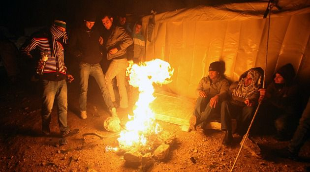 E1 Eviction: Palestinians keep warm around a fire in the camp in the E1 section of the West Bank. Israel started to remove the protesters Sunday.