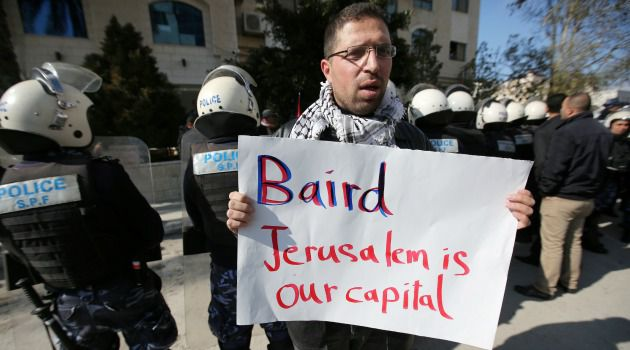 Egging Them On? Policemen stand guard as a Palestinian protester holds a placard outside the Foreign Affairs ministry where Palestinian Minister of Foreign Affairs Riyad al-Maliki meets his Canadian counterpart John Baird.