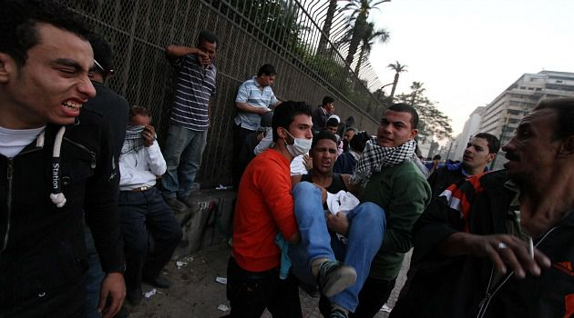 Deep Divisions: Opponents of Mohammed Morsi help injured protester in streets of Cairo.
