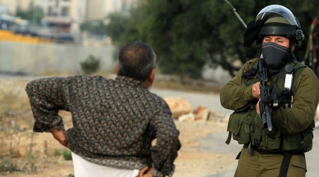 Searching Look: Israeli soldier checks Palestinian man in the occupied West Bank.