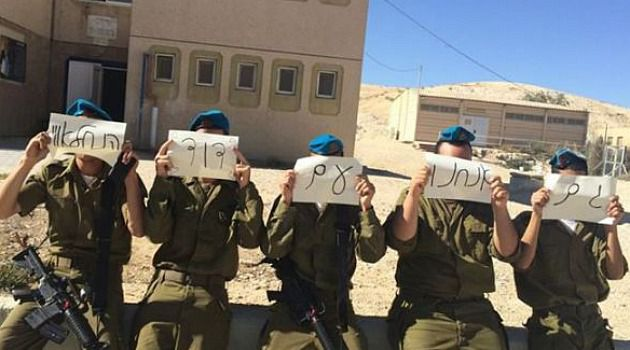 Stand With Him: Israeli soldiers hold signs supporting comrade who was punished for pointing a gun at a Palestinian teenager.